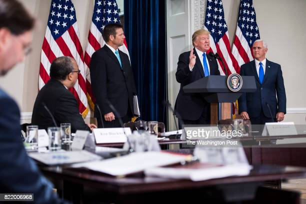 President Donald Trump accompanied by Vice President Mike Pence right and Kansas Secretary of State Kris Kobach center left speaks at the first...