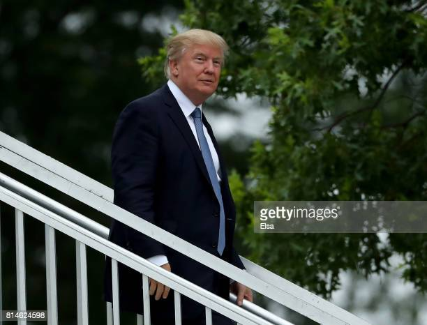 S President Donald Trump acknowledges the patrons in the clubhouse as he leaves the US Women's Open round two on July 14 2017 at Trump National Golf...
