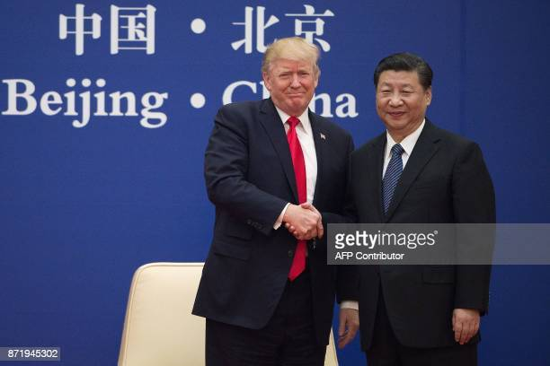 US President Donald Trump and China's President Xi Jinping shake hands during a business leaders event at the Great Hall of the People in Beijing on...