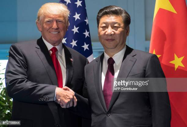 US President Donald Trump and Chinese President Xi Jinping shake hands prior to a meeting on the sidelines of the G20 Summit in Hamburg Germany July...