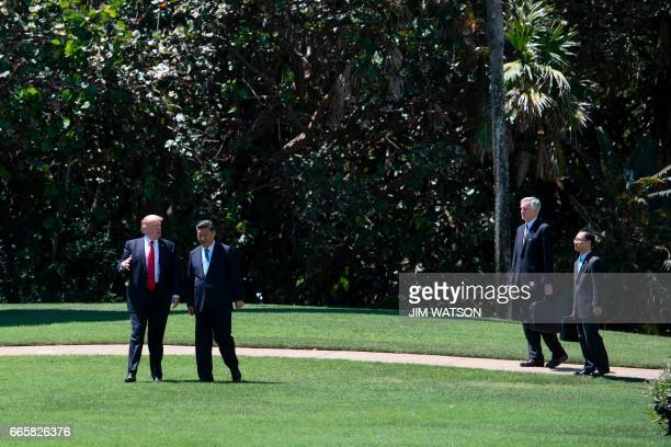 US President Donald Trump and Chinese President Xi Jinping walk together followed by interpreters at the MaraLago estate in West Palm Beach Florida...
