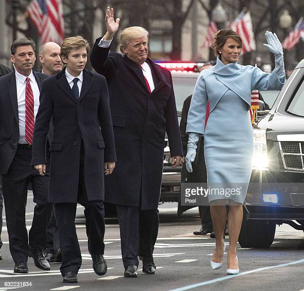 President Donald Trump and first lady Melania Trump along with their son Barron walk in their inaugural parade on January 20 2017 in Washington DC...
