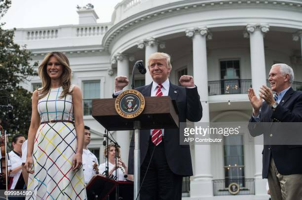 US President Donald Trump and First Lady Melania Trump are applauded by Vice President Mike Pence as they arrive at the Congressional picnic at the...