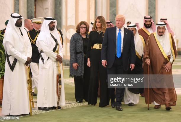 US President Donald Trump and First Lady Melania Trump are escorted by Saudi Arabia's King Salman bin Abdulaziz alSaud as they arrive at the Saudi...