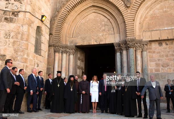 US President Donald Trump and First Lady Melania Trump are greeted by priests and others as they arrive for their visit at the Church of the Holy...
