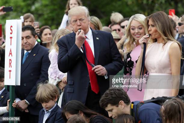 S President Donald Trump and first lady Melania Trump blow whistles to kickoff a race during host the 139th Easter Egg Roll with Trump's daughter...