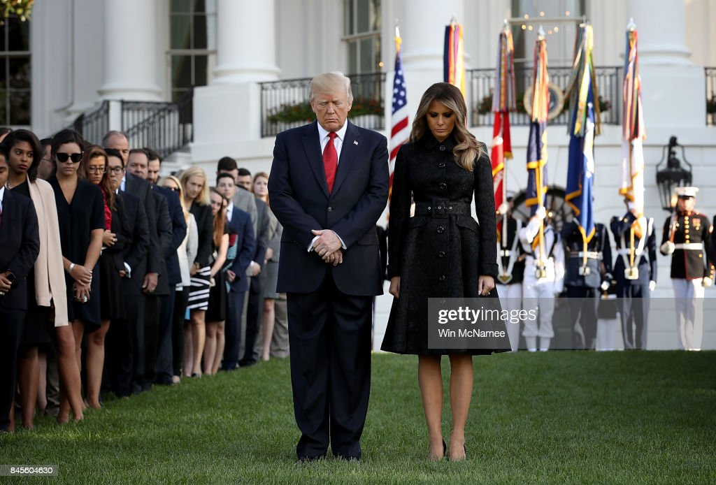 U.S. President Donald Trump and first lady Melania Trump, flanked by White House staff, observe a moment of silence on the South Lawn of the White House for the September 11 terrorist attacks September 11, 2017 in Washington, DC. Today marks the 16th anniversary of the attacks that killed almost 3,000 people and wounded another 6,000.