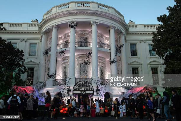 President Donald Trump and First Lady Melania Trump hand out candy to children during a Halloween event at the White House in Washington DC on...