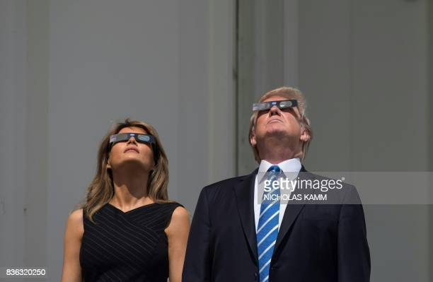 US President Donald Trump and First Lady Melania Trump look up at the solar eclipse from the balcony of the White House in Washington DC on August 21...