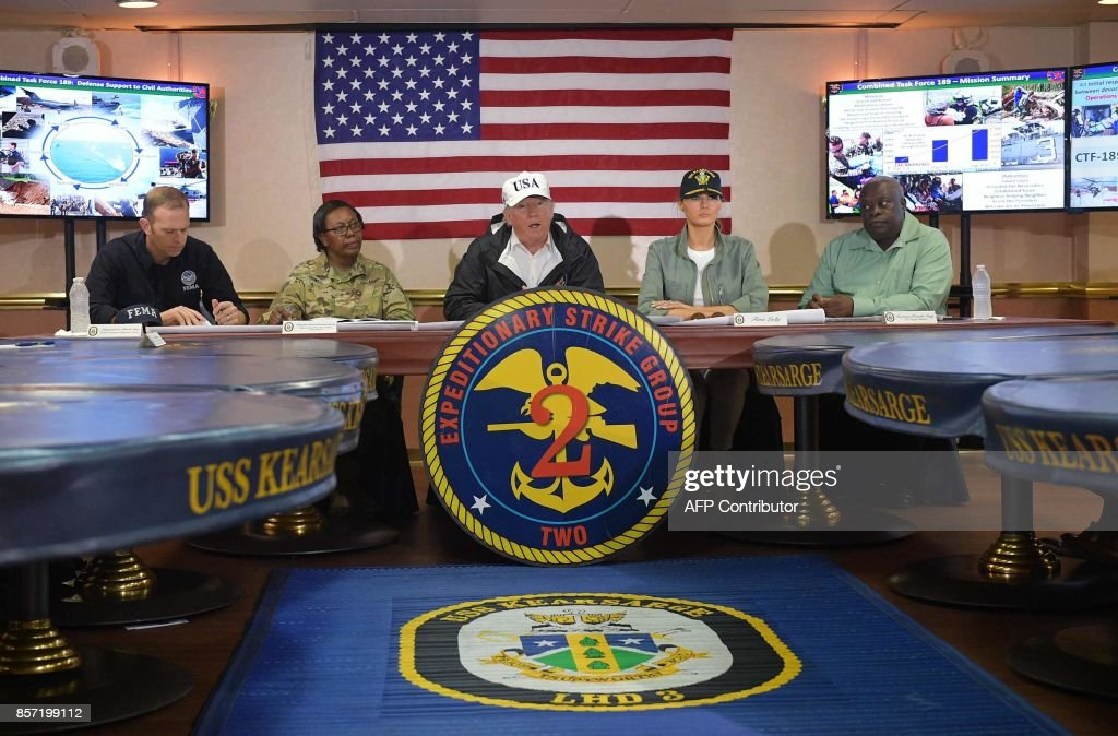 US President Donald Trump and First Lady Melania Trump meet with US Virgin Islands Governor Kenneth Mapp (R) in the Ward Room aboard the USS Kearsarge, off Puerto Rico on October 3, 2017. Nearly two weeks after Hurricane Maria thrashed through the US territory, much of the islands remains short of food and without access to power or drinking water. /