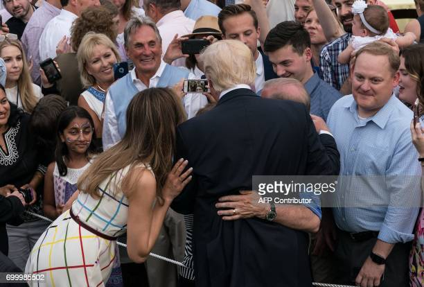 US President Donald Trump and First Lady Melania Trump pose for a photo with guests at the Congressional picnic at the White House in Washington DC...