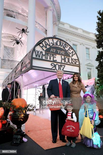 S President Donald Trump and first lady Melania Trump pose for photographs while hosting Halloween at the White House on the South Lawn October 30...