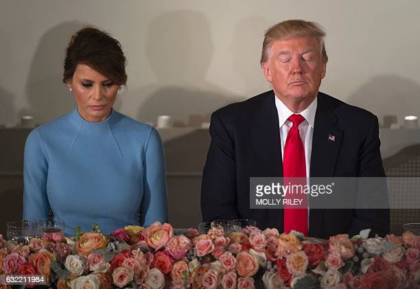 President Donald Trump and First Lady Melania Trump pray during the Inaugural Luncheon at the US Capitol following Donald Trump's inauguration as the...