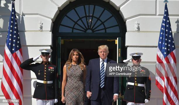 US President Donald Trump and First Lady Melania Trump step out of the South Portico to take part in a moment of silence for the victims of the Las...