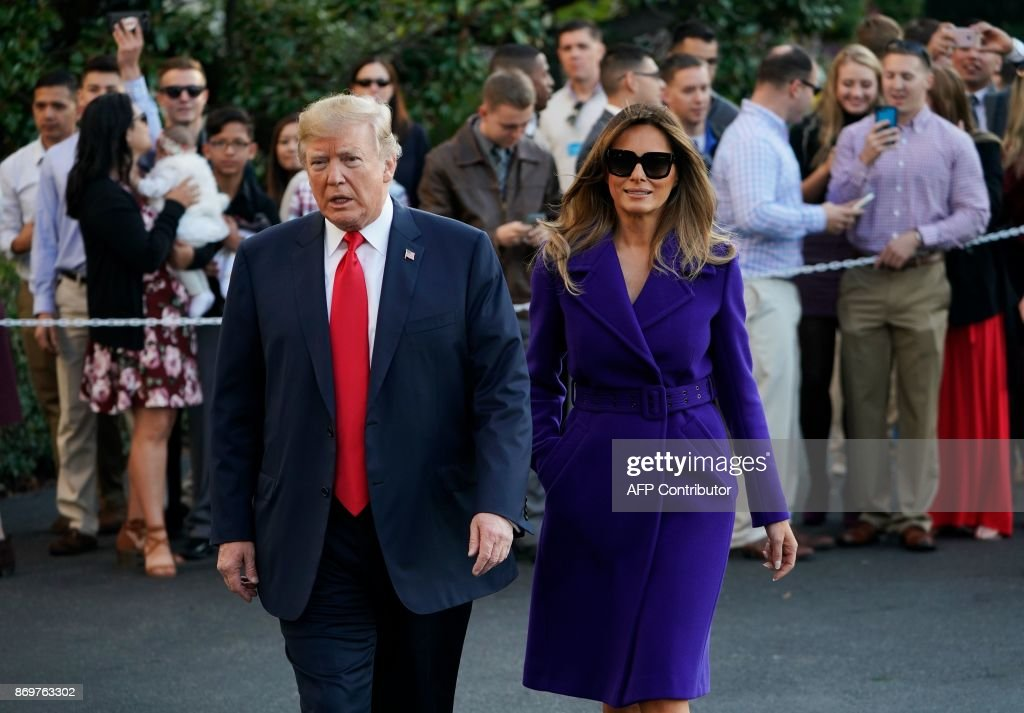 President Donald Trump and First Lady Melania Trump walk towards reporters before departing from the South Lawn of the White House on November 3, 2017 in Washington, DC, embarking on a 11-day tour of Asia. /