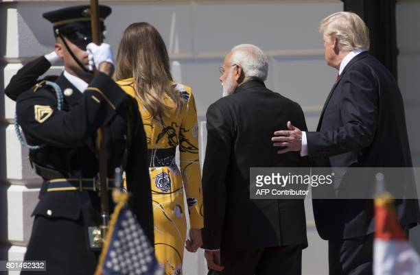 US President Donald Trump and First Lady Melania Trump walk with Indian Prime Minister Narendra Modi after his arrival on the South Lawnat The White...