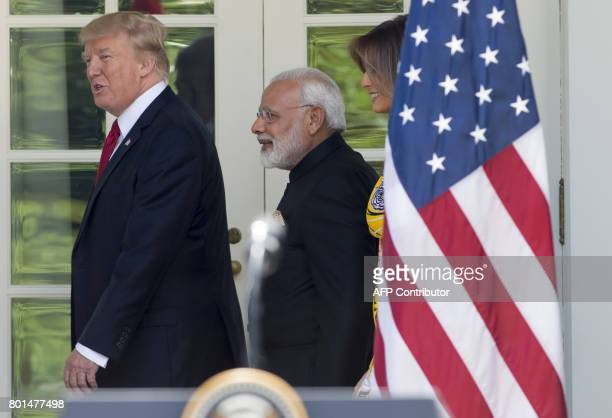 US President Donald Trump and First Lady Melania Trump walk with Indian Prime Minister Narendra Modi along the West Wing Colonnade past the Rose...