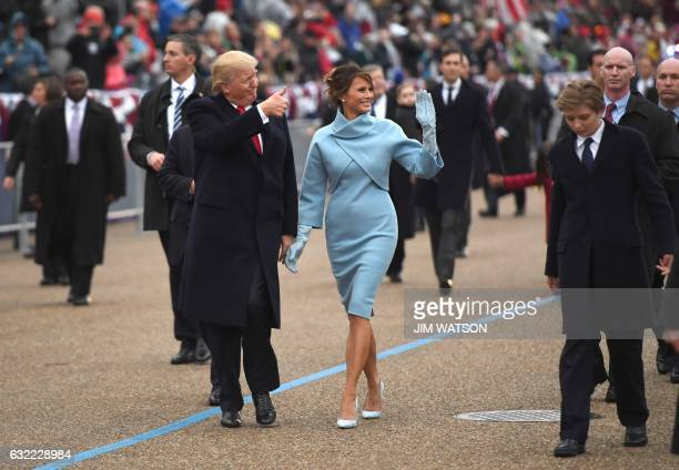US President Donald Trump and First Lady Melania walk the inaugural parade route with son Barron on Pennsylvania Avenue in Washington DC on January...
