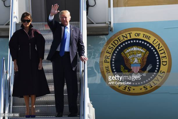 US President Donald Trump and First Lady Melania wave from Air Force One prior to departing from US Yokota Air Base in Tokyo on November 7 2017...