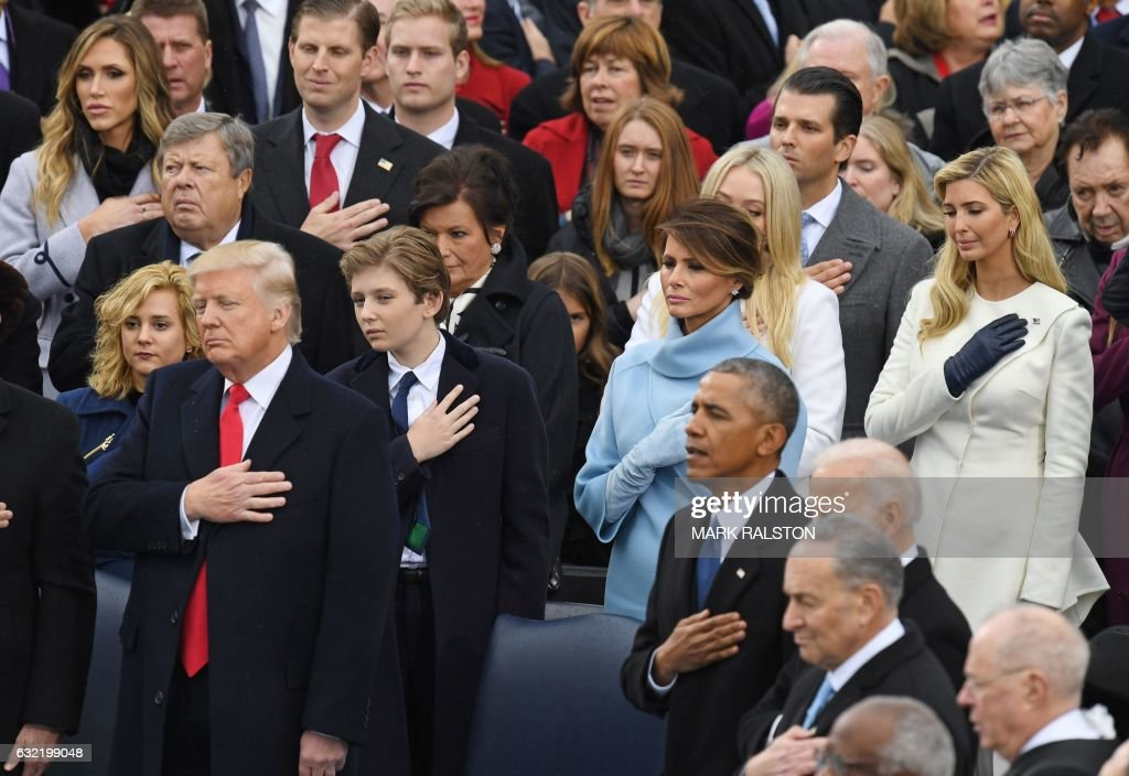 President Donald Trump (L) and former US President Barack Obama cross their hearts during the National Anthem sung at Trump's swearing-in ceremony on January 20, 2017 at the US Capitol in Washington, DC. / AFP PHOTO / Mark RALSTON