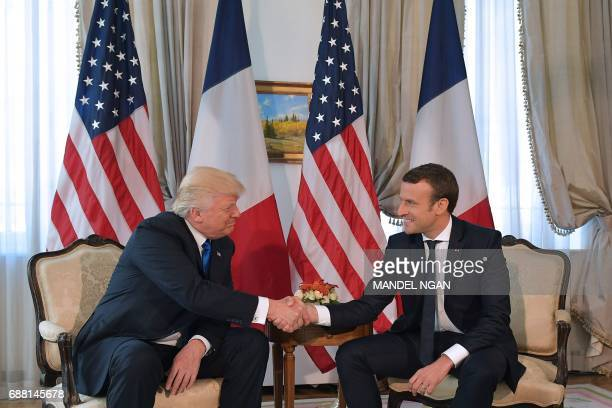 US President Donald Trump and French President Emmanuel Macron shake hands ahead of a working lunch at the US ambassador's residence on the sidelines...