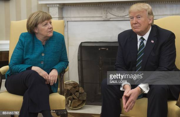 President Donald Trump and German Chancellor Angela Merkel meet in the Oval Office of the White House in Washington DC on March 17 2017 / AFP PHOTO /...