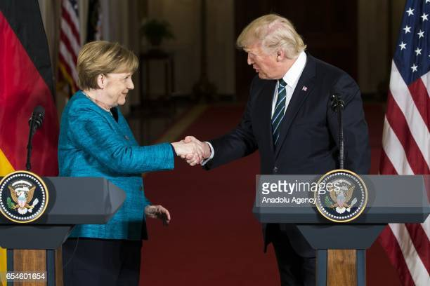 S President Donald Trump and German Chancellor Angela Merkel shake their hands after the joint press conference at the White House during Chancellor...
