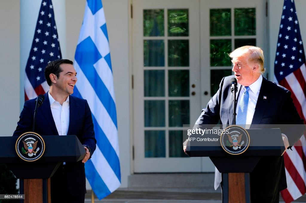 US President Donald Trump (R) and Greek Prime Minister Alexis Tsipras share a laugh while addressing the media in the Rose Garden at the White House in Washington, DC. on October 17, 2017. / AFP PHOTO / Jason Connolly