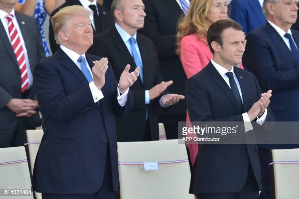 US President Donald Trump and his French counterpart Emmanuel Macron applaud as they watch the annual Bastille Day military parade on the...