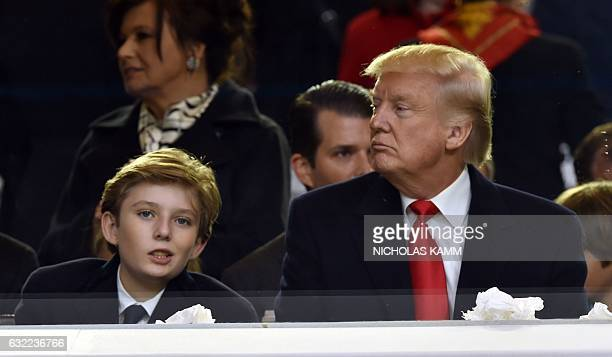 US President Donald Trump and his son Baron attend the presidential inaugural parade on January 20 2017 in Washington DC / AFP / Nicholas Kamm