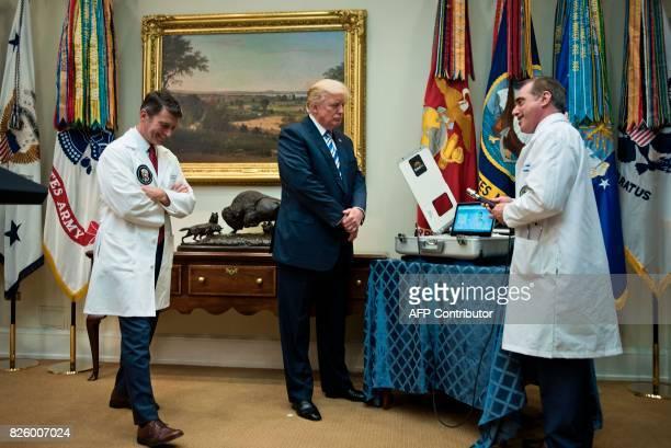US President Donald Trump and his White House physician Dr Ronny Jackson listen as US Secretary of Veterans Affairs David J Shulkin speaks about new...