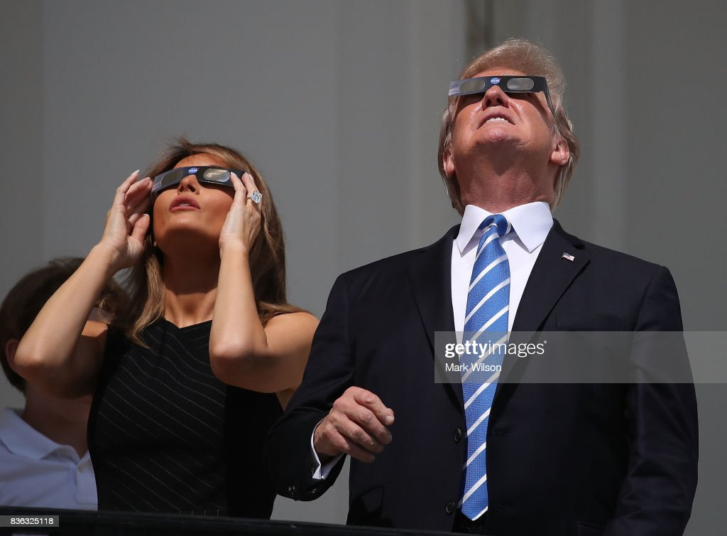 US President Donald Trump and his wife first lady Melania Trump wear special glasses to view the solar eclipse at the White House on August 21, 2017 in Washington, DC. Millions of people have flocked to areas of the U.S. that are in the 'path of totality' in order to experience a total solar eclipse.