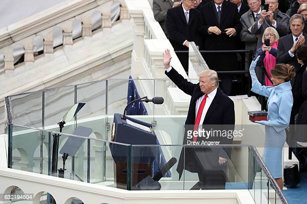 S President Donald Trump and his wife Melania Trump wave after he took the oath of office on the West Front of the US Capitol on January 20 2017 in...