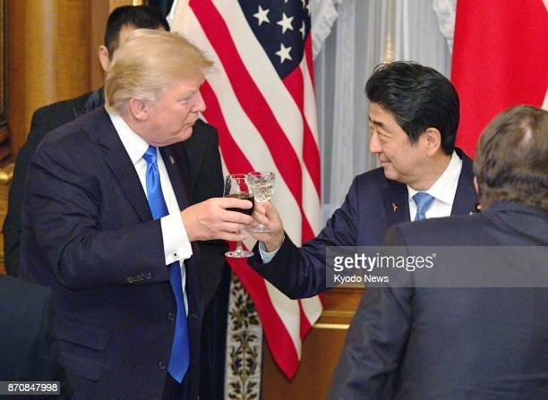US President Donald Trump and Japanese Prime Minister Shinzo Abe clink their glasses at a dinner party at the Akasaka Palace state guesthouse in...
