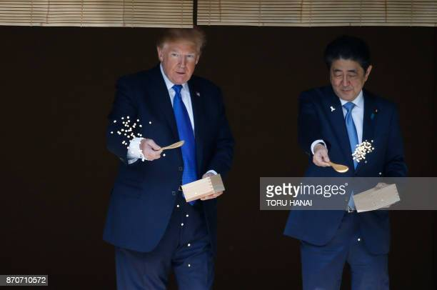 US President Donald Trump and Japanese Prime Minister Shinzo Abe feed koi fish during a welcoming ceremony in Tokyo on November 6 2017 Trump lashed...