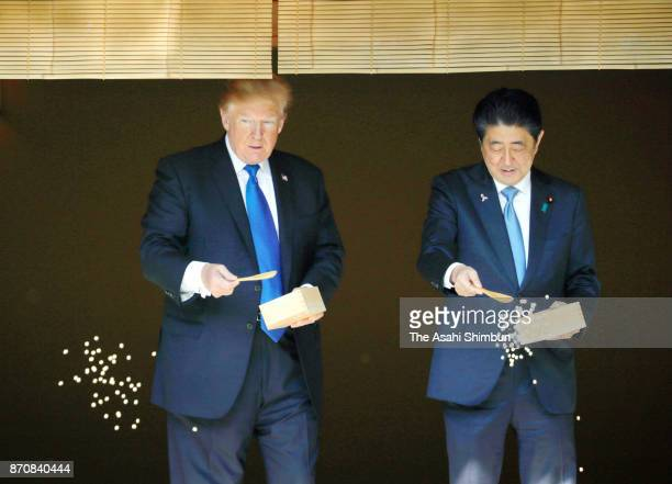 US President Donald Trump and Japanese Prime Minister Shinzo Abe feed carps prior to a working lunch at the Akasaka State Guest House on November 6...