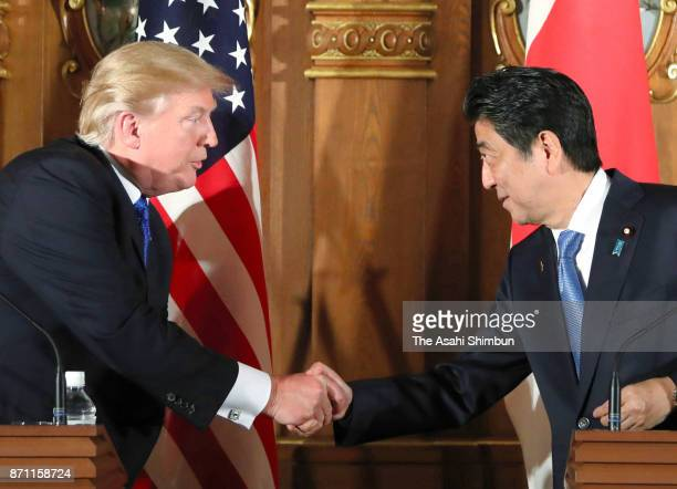 US President Donald Trump and Japanese Prime Minister Shinzo Abe shake hands during a joint press conference following their meeting at the Akasaka...