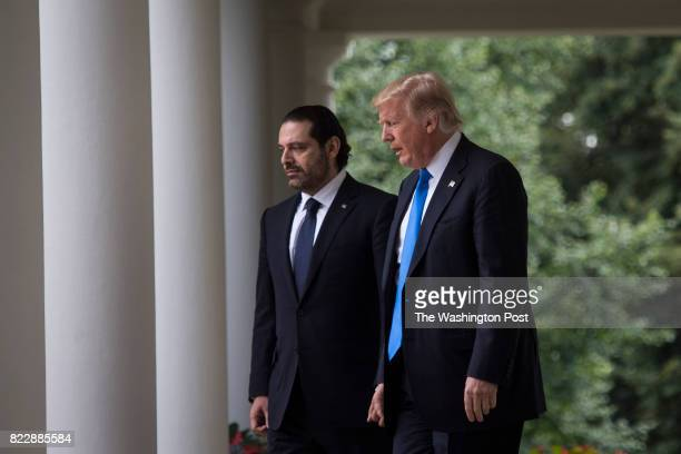 President Donald Trump and Lebanese Prime Minister Saad Hariri walk to the Rose Garden for a joint news conference at the White House in Washington...
