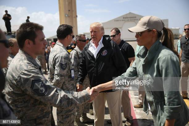 President Donald Trump and Melania Trump greet US Air Force airmen as he arrives at the Muniz Air National Guard Base as he makes a visit after...
