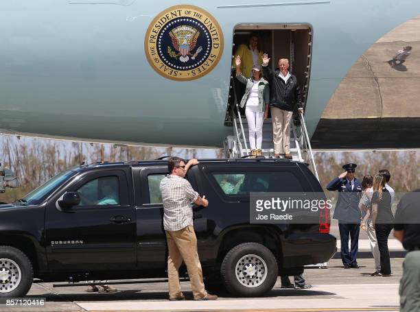 President Donald Trump and Melania Trump wave as they arrive on Air Force One at the Muniz Air National Guard Base for a visit after Hurricane Maria...