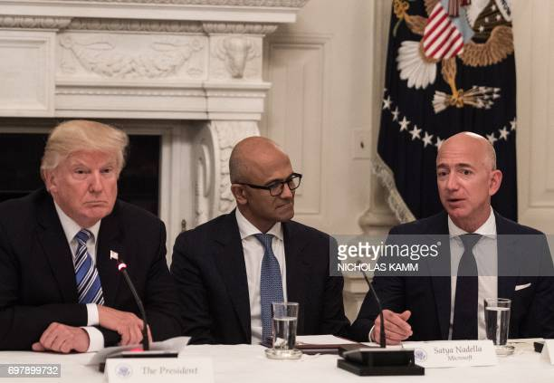 US President Donald Trump and Microsoft CEO Satya Nadella listen to Amazon CEO Jeff Bezos during an American Technology Council roundtable at the...