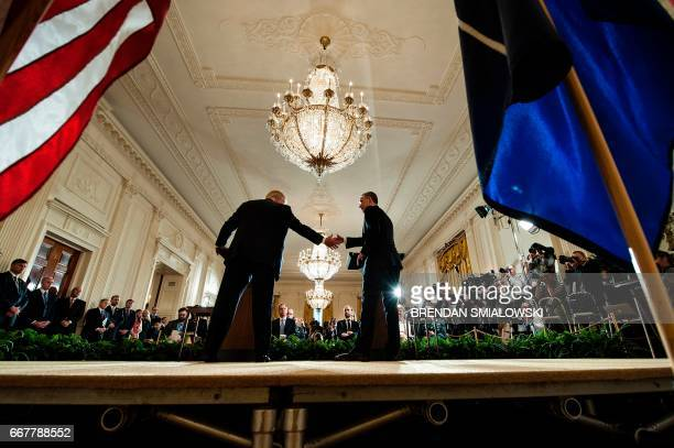 US President Donald Trump and NATO Secretary General Jens Stoltenberg shake hands following a joint press conference in the East Room at the White...