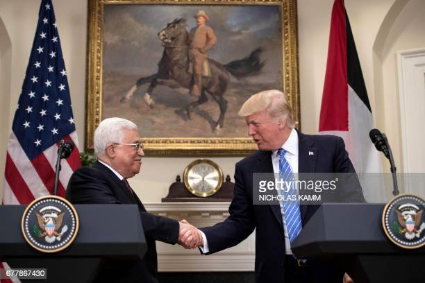 US President Donald Trump and Palestinian Authority President Mahmud shake hands in the Roosevelt Room during a joint statement at the White House in...