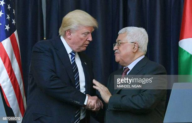 US President Donald Trump and Palestinian leader Mahmud Abbas shake hands during a joint press conference at the presidential palace in the West Bank...