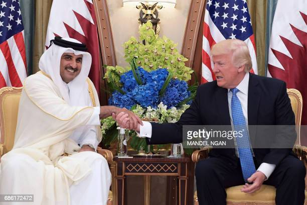 US President Donald Trump and Qatar's Emir Sheikh Tamim Bin Hamad AlThani take part in a bilateral meeting at a hotel in Riyadh on May 21 2017 / AFP...