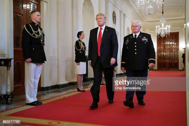 S President Donald Trump and retired US Army Capt Gary Rose walk into the East Room for his Medal of Honor ceremony at the White House October 23...