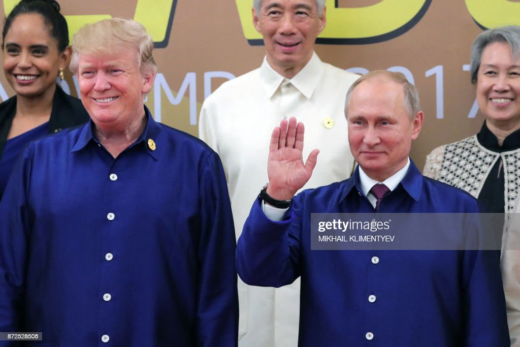 US President Donald Trump (L) and Russia's President Vladimir Putin (R) pose for a group photo ahead of the Asia-Pacific Economic Cooperation (APEC) Summit leaders gala dinner in the central Vietnamese city of Danang on November 10, 2017. / AFP PHOTO / SPUTNIK / Mikhail KLIMENTYEV