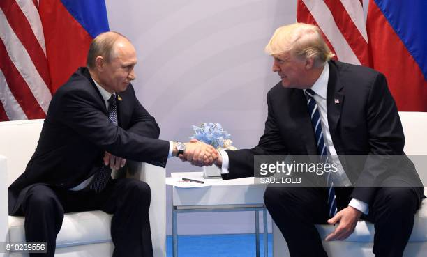 US President Donald Trump and Russia's President Vladimir Putin shake hands during a meeting on the sidelines of the G20 Summit in Hamburg Germany on...