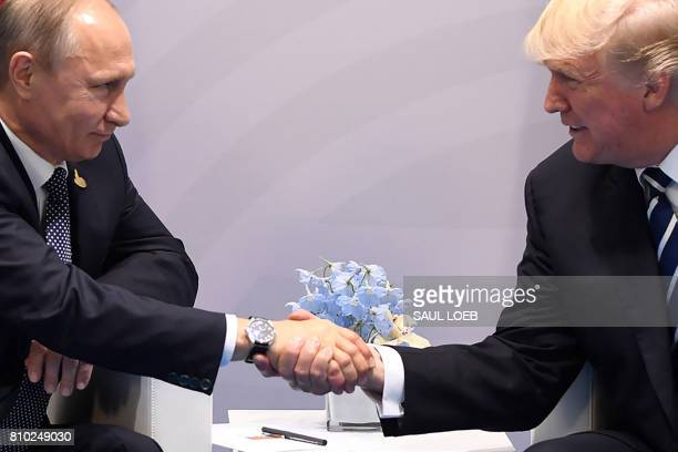 President Donald Trump and Russia's President Vladimir Putin shake hands during a meeting on the sidelines of the G20 Summit in Hamburg Germany on...