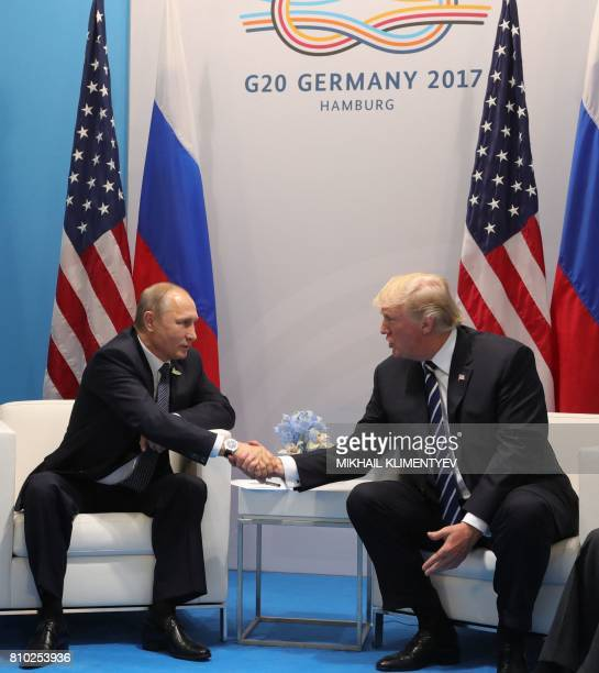 US President Donald Trump and Russia's President Vladimir Putin shake hands as they hold a meeting on the sidelines of the G20 Summit in Hamburg...
